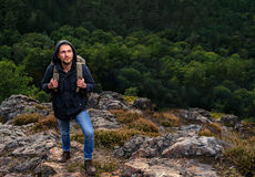 Hipster young man with backpack enjoying mountain. Tourist traveler on background view forest. mock up text. Picos de Stock Image