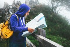 Hipster young man with backpack holding in hands and looking on map spain of foggy mountain, tourist traveler hiker on background stock photography
