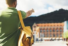 Hipster young man with backpack and map. View from back tourist traveler planning route on background sun city and pointing hand. Route. Person hiker visiting stock photo