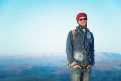 Hipster young man with beard and mustache wearing sunglasses posing against the background of mountains royalty free stock image