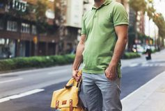 Hipster young man holding in hands backpack with map. Front view tourist traveler planning route and standing at the road on back. Ground sun summer street royalty free stock photography