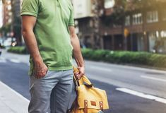 Hipster young man holding in hands backpack with map. Front view tourist traveler planning route and standing at the road on back. Ground sun summer street royalty free stock image