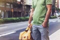 Hipster young man holding in hands backpack with map. Front view tourist traveler planning route and standing at the road on back. Ground sun summer street royalty free stock photo