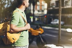 Hipster young man holding in hands backpack and map. Side view tourist traveler planning route on background sun and orange moto royalty free stock images