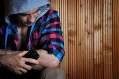 Hipster young man in the hood, sitting, holds phone and look down on wooden brown background. With copy space right Stock Images