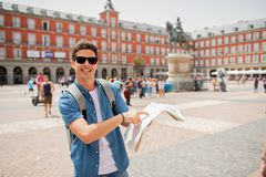 Good looking young man traveler holding up a map in madrid. Hipster young man traveler traveling in Madrid holing up a map in the plaza major in tourist travel Stock Image