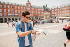 Good looking young man traveler holding up a map in madrid. Hipster young man traveler traveling in Madrid holing up a map in the plaza major in tourist travel Royalty Free Stock Photography