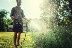 Hipster young man watering plants in a country house, summer and garden care royalty free stock photos