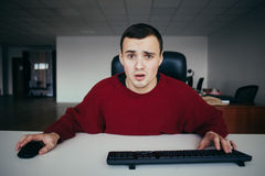 Hipster young man working in the office puzzled looks at the monitor of your computer. Interested in camera view Stock Photos