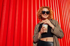Hipster young woman with curly red hair drinking coffee against red wall. Stylish summer girl in sunglasses smiling. And relaxing outdoors Stock Images