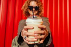 Hipster young woman with curly red hair holding coffee against red wall. Close-up of plastic cup. Hipster young woman with curly red hair holding coffee against Stock Photos