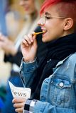 Hipster young woman eating potatoes while her friend using the smartphone in the street. Stock Image
