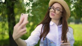 Ginger girl in glasses and straw hat making a selfie in park stock video