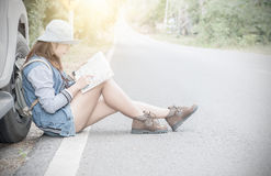 Hipster young woman looking for way during her road-trip from ma Royalty Free Stock Photos