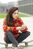 Hipster young woman sitting on skateboard with phone. Stock Photo