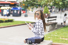Hipster young woman traveling and taking notes in the stret. Stock Image
