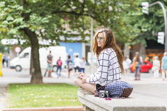 Hipster young woman traveling and taking notes in the stret. Royalty Free Stock Images
