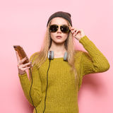 Hipster young woman using cell phone and selecting music to listen on headphones. Stock Photo