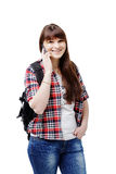 Hipster young woman waiting for someone and using smartphone on white background. Travel vacation getaway trip concept. Hipster young woman communicates via a Royalty Free Stock Image