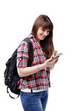 Hipster young woman waiting for someone and using smartphone on white background. Travel vacation getaway trip concept. Hipster young woman communicates via a Royalty Free Stock Photo