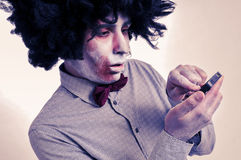 Hipster zombie with an afro using a smartphone, with a filter ef Royalty Free Stock Photo