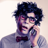Hipster zombie talking on the phone, with a retro effect. A scary hipster zombie with black plastic-rimmed eyeglasses talking on the phone, with a retro effect stock photo