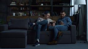 Hipsterbästa vän med smartphones på soffan stock video