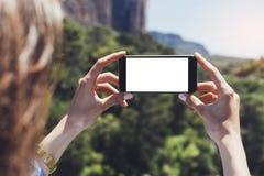 Hipsterbloggerflickan rymmer mobiltelefonen i kvinnliga händer, tar fotobilden av det naturliga landskapet på ett soligt lopp för arkivbild