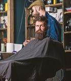 Hipstercli?nt die kapsel krijgen Het concept van het kapselproces Mens met baard met zwart kaapwachten wordt behandeld terwijl ka royalty-vrije stock afbeelding