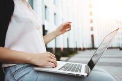 Hipsteren för den unga kvinnan sitter i utomhus- på stads- och maskinskrivningtext på den moderna bärbara datorn royaltyfri bild