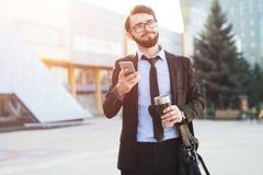 Hipsteren imponerade affärsmannen som använder smartphonen på kontorsbyggandebakgrund med thermo kaffe, rånar i hand och svart på fotografering för bildbyråer