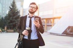 Hipsteren imponerade affärsmannen som använder smartphonen på kontorsbyggandebakgrund med thermo kaffe, rånar i hand och svart på royaltyfria foton