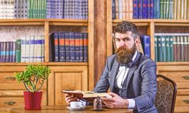 Hipsteren läser att intressera boken i en trevlig tappning caf royaltyfri bild