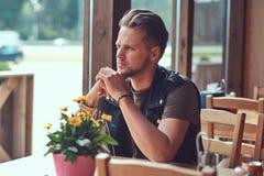 Hipsteren med en stilfullt frisyr och skägg sitter på en tabell i ett vägrenkafé, ser gatan arkivbilder