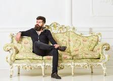 Hipsteren på arrogant framsida sitter bara Mannen med skägget och mustaschen spenderar fritid i lyxig vardagsrum Rikt och ensamt royaltyfria foton
