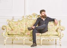 Hipsteren på arrogant framsida sitter bara Mannen med skägget och mustaschen spenderar fritid i lyxig vardagsrum Rikt och ensamt fotografering för bildbyråer