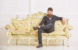 Hipsteren på strikt framsida sitter bara Rikt och ensamt begrepp Ägaren av den lyxiga lägenheten sitter på soffan, den vita vägge fotografering för bildbyråer