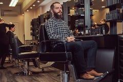 Hipsteren uppsökte mannen i en flanellskjorta och jeans som sitter på en barberarestol, når han har klippt i en friseringsalong Royaltyfri Fotografi