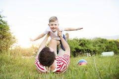 Hipsterfader och liten son på grön äng solig dagsommar fotografering för bildbyråer