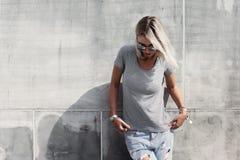 Hipsterflicka i grå t-skjorta över gataväggen royaltyfria bilder
