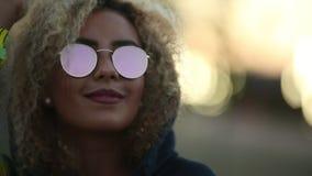 Hipsterflicka med lockigt blont hår och spegelförsedd solglasögon som ser bort och le stock video