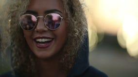 Hipsterflicka med lockigt blont hår och spegelförsedd solglasögon som ser bort och le arkivfilmer