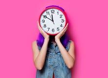 Hipsterflicka med purpurfärgat hår och den stora klockan Royaltyfri Bild