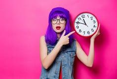 Hipsterflicka med purpurfärgat hår och den stora klockan Arkivfoto