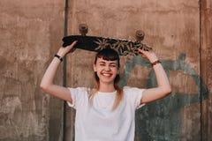 Hipsterflicka med skridskobrädet Royaltyfri Foto