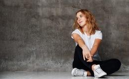 Hipsterflicka som bär den tomma vita t-skjortan, jeans mot väggen, royaltyfria foton