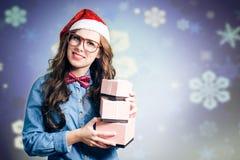 Hipsterflicka som bär hatten för xmas som santa rymmer tre arkivbild