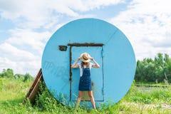Hipsterflicka som döljer hennes framsida bak en hatt Spela utomhus på en härlig solig sommardag Royaltyfri Foto