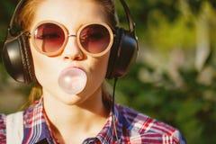 Hipsterflicka som lyssnar till musik på hörlurar och tuggningar bollen av idisslad föda arkivbild