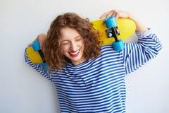 Hipsterflicka som skrattar med skateboarden royaltyfri fotografi